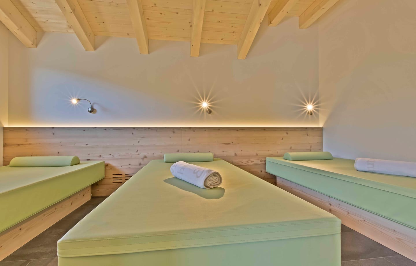 The relaxation area in the wellness space overlooks the magnificent woods of San Cassiano.